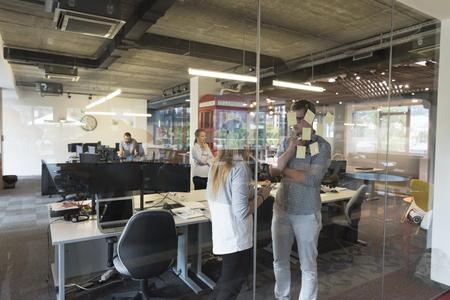 oficina: poner en marcha la planificación y organización de empresas toma con joven pareja en la redacción de notas modernas interior de la oficina en las etiquetas adhesivas