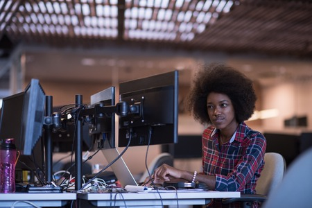 young black woman at her workplace in modern office  relaxing and working on laptop computer with dual monitor screen Banco de Imagens - 67214234