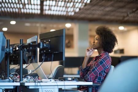 リラックスしてデュアル モニター画面のラップトップ コンピューターに取り組んでいる近代的なオフィスに彼女の職場の若い黒人女性