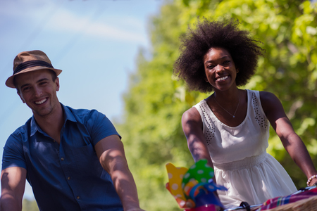 young happy couple: a young man and a beautiful black girl enjoying a bike ride in nature on a sunny summer day Stock Photo