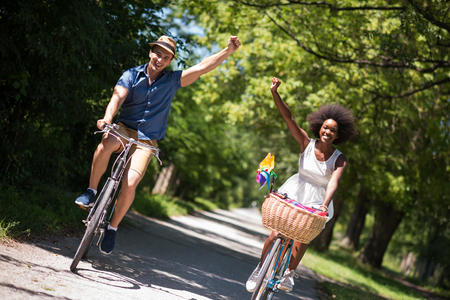 black couple: a young man and a beautiful black girl enjoying a bike ride in nature on a sunny summer day Stock Photo