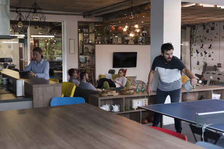 mid thirties: Two young start up business man playing ping pong tennis at modern creative office space  people group have meeting and brainstorming in background Stock Photo