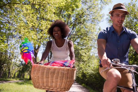 a young man and a beautiful black girl enjoying a bike ride in nature on a sunny summer day Stock Photo