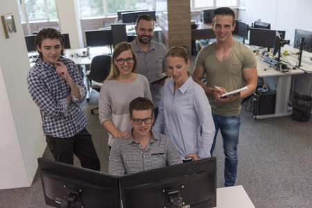 looking at computer: group of young startup business people standing as team at office desk while working on everyday job