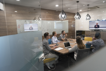 opstarten bedrijfsgroep mensen het bijwonen van een videoconferentie call met senior investitior op modern kantoor