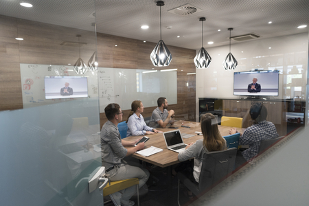conference call: start up business people group attending videoconference call with senior investitior at modern office