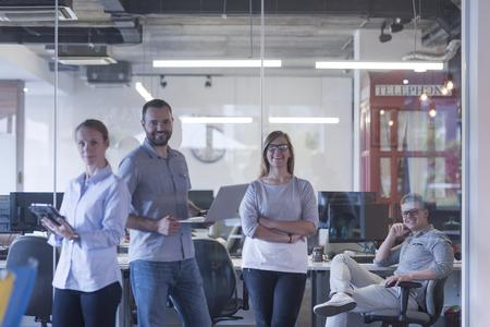 standing up: start up business team portrait at modern office interior
