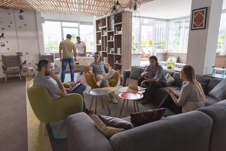 Gruppe der jungen Leute in der modernen Büro-Team Treffen und Brainstorming während der Arbeit am Laptop und Kaffee zu trinken