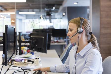 職場でヘッドセットを持つ女性の顧客サポート電話オペレータ