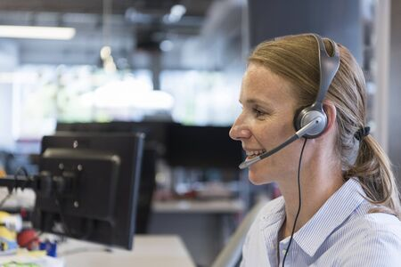 customer support: female customer support phone operator with headset  at workplace Stock Photo