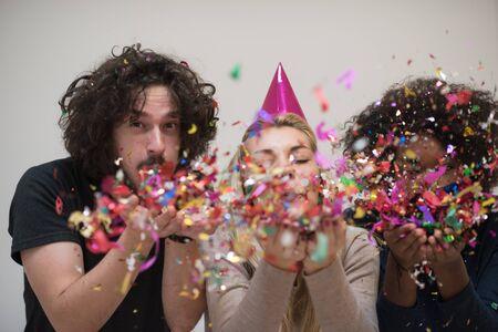 紙吹雪幸せな若い連中が踊りながら祝う大晦日をグループ化し、家庭で楽しい時を過す