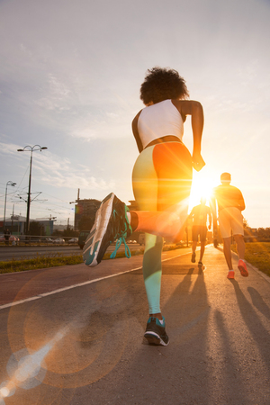 outdoor fitness: young black girl on the jogging beautiful morning as the sun rises in the streets of the city