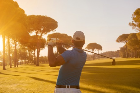 バック グラウンドで太陽フレアと美しい朝コースのクラブでショットを打つゴルフ プレーヤー
