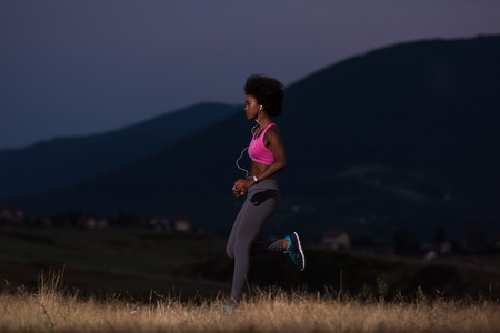 jonge Afro-Amerikaanse vrouw runner met een koptelefoon joggen buiten in de natuur mooie zomeravond - Fitness, mensen en een gezonde levensstijl