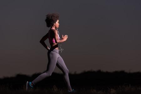 hacer footing: joven corredor de la mujer del afroamericano con los auriculares que activan al aire libre en la naturaleza hermosa noche de verano - la aptitud, la gente y el estilo de vida saludable