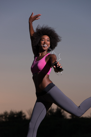 american sport: Young healthy black woman is doing stretching exercise relaxing and warm up after jogging and running in the nature beautiful summer evening