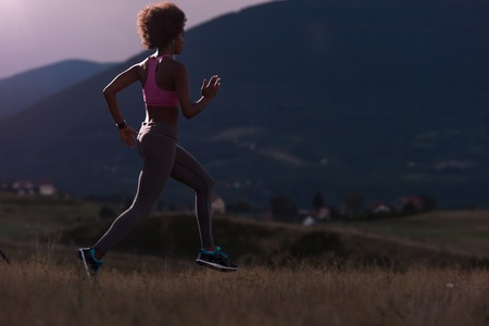 hacer footing: young African american woman runner with headphones jogging outdoors in nature beautiful summer night - Fitness, people and healthy lifestyle