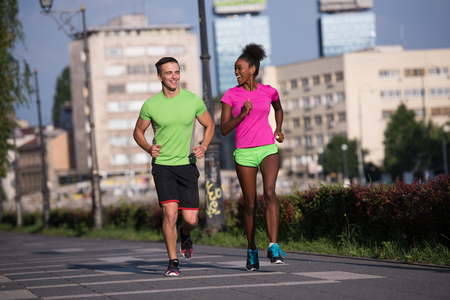 healthy young multiethnic couple jogging in the city on a sunny summer day Banco de Imagens - 67136460