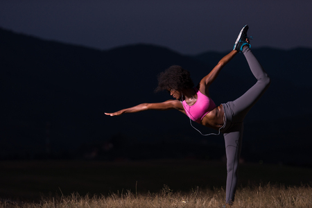 american sport: young beautiful black woman doing yoga exercises in the nature of a beautiful summer night