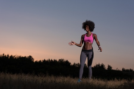 negro mujer sana joven está haciendo ejercicios de estiramiento relajante y calentarse después de trotar y correr en la naturaleza hermosa tarde de verano