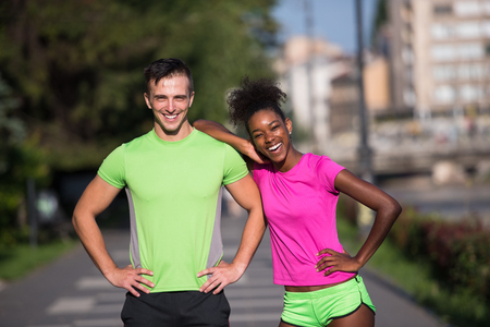 mujeres fitness: portrait of young multietnic jogging couple ready to run on fresh morning in the city