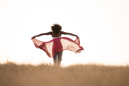 Young beautiful black girl laughs and dances outdoors with a scarf in her hands in a meadow during sunset 版權商用圖片