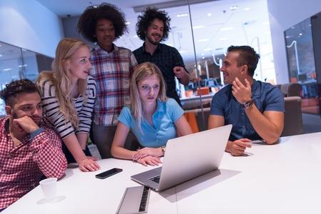 equipe de negócios de inicialização multiétnica em atender no moderno e luminoso de brainstorming interior do escritório, trabalhando no laptop e tablet computador