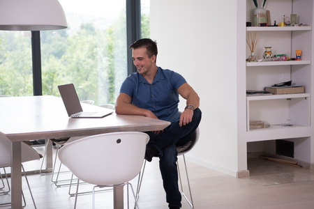 laptop home: Young man with his laptop computer at his luxury modern home, smiling