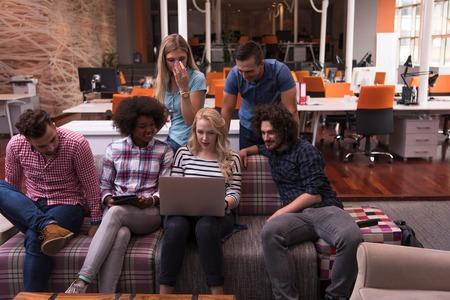 ノート パソコンやタブレット コンピューターで作業して、近代的な明るいオフィス インテリア ブレーンストーミング会議多民族スタートアップ事