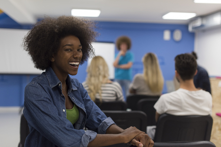 focus group: portrait of young African American business woman at modern startup office interior, team in meeting in background