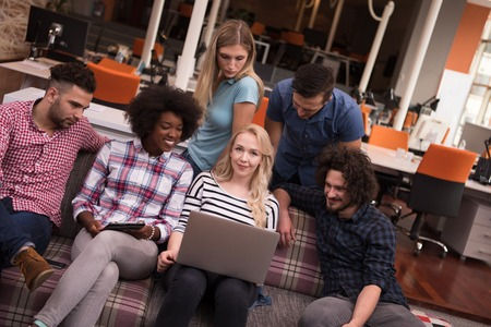Multiétnico equipo de negocios de inicio en el cumplimiento de moderno y luminoso de reflexión interior de la oficina, trabajando en equipo portátil y la tableta de ordenador