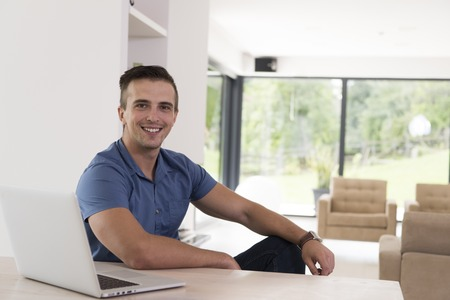 his: Young man with his laptop computer at his luxury modern home, smiling