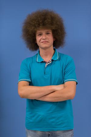 Porträt eines jungen Mannes mit einer funky Frisur mit verschränkten Armen auf blauem Hintergrund