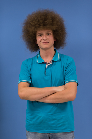 portrait of a young man with a funky hairstyle with arms crossed on blue background Stock fotó