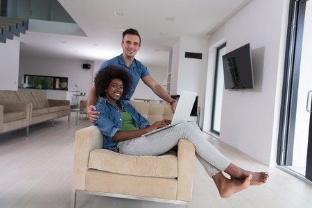 Young multiethnic couple sitting on an armchair in the luxury living room, using a laptop computer Stock Photo