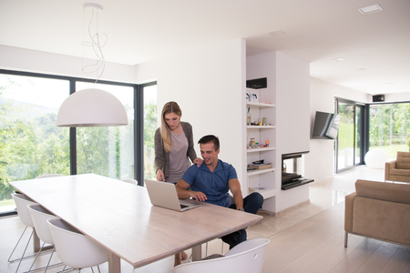 laptop home: Young couple using laptop computer at luxury home together, looking at screen, smiling. Stock Photo