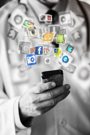 Hand met slimme telefoon en sociaal netwerk pictogrammen vliegen Stockfoto