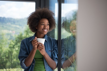 looking out: Beautiful young african american woman drinking coffee and looking through a window in her luxury home