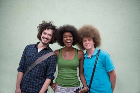 people laughing: Portrait of multiethnic group of happy three friends in casual wear standing and laughing