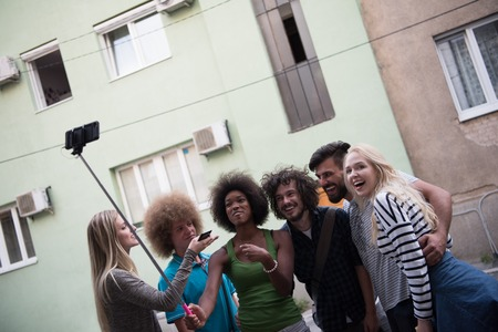selfy: Multiethnic Group of friends taking picture of themselves with smartphone Stock Photo