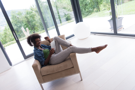 young beautiful African American woman enjoys listening to music with headphones and tablet in your armchair in her luxury home Stock Photo