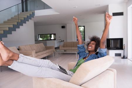listening to music: joven y bella mujer afroamericana le gusta escuchar música con auriculares y la tableta en su sillón en su casa de lujo