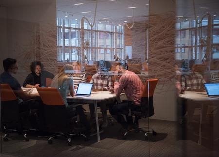 Equipo de negocios de inicio multiétnico en la reunión en la oficina moderna brillante interior de intercambio de ideas, trabajando en equipo portátil y tableta