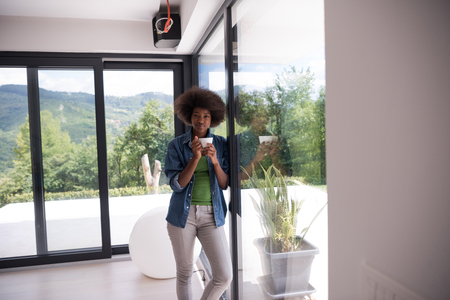 looking through window: Beautiful young african american woman drinking coffee and looking through a window in her luxury home