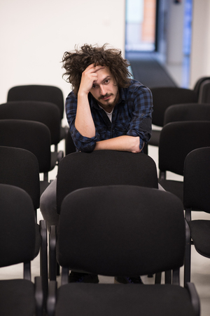 freshmen: A student sits alone in a empty seats in a classroom