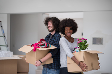 black couple: Happy young multiethnic couple unpacking or packing boxes and moving into a new home