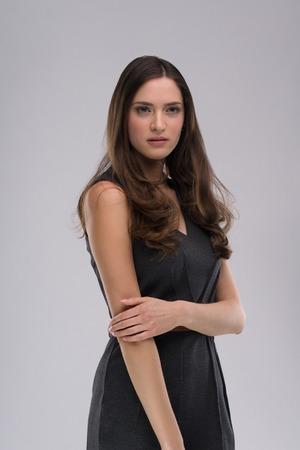 mujer sola: hermosa mujer morena posando en un vestido gris y expresa diferentes emociones. Primer plano retrato