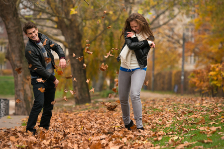 Happy young Couple in Autumn Park. Fall. Yellow Trees and Leaves. Laughing Man and Woman outside. Freedom Concept.