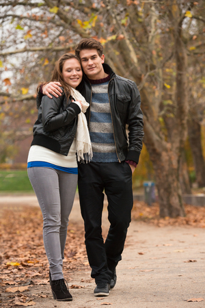 pareja abrazada: Happy young Couple in Autumn Park. Fall. Yellow Trees and Leaves. Laughing Man and Woman outside. Freedom Concept.