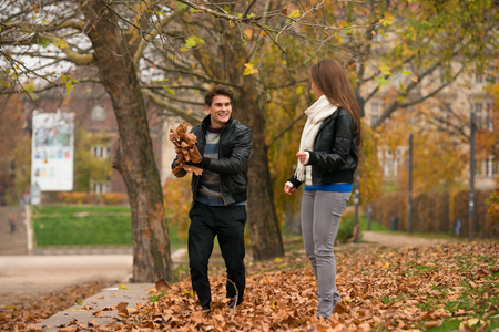 yellow trees: Happy young Couple in Autumn Park. Fall. Yellow Trees and Leaves. Laughing Man and Woman outside. Freedom Concept.